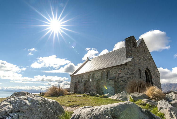 the good shepherd in new zealand Church Architecture Bright Building Building Exterior Built Structure Cloud - Sky Day Land Lens Flare Low Angle View Nature No People Outdoors Rock Rock - Object Sky Solid Sun Sunbeam Sunlight Sunny The Good Shepherd Water