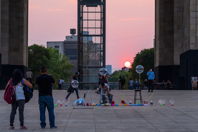 Group of people playing against buildings in city at sunset