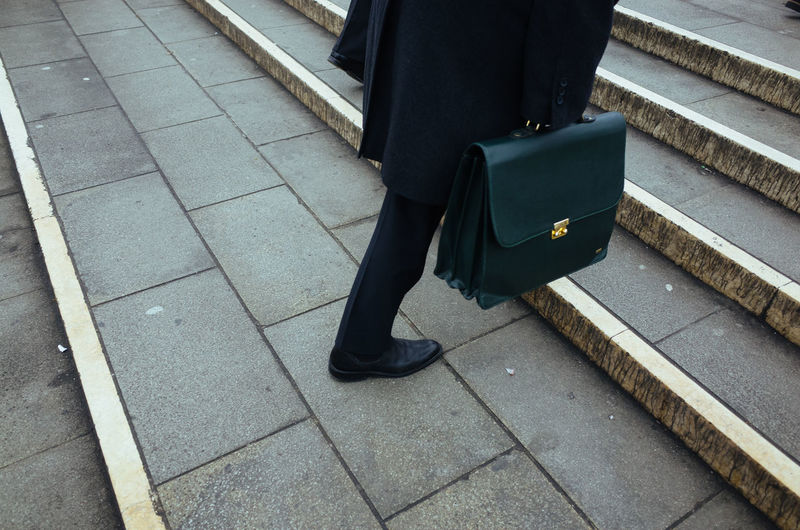 Low section of businessman with briefcase on steps