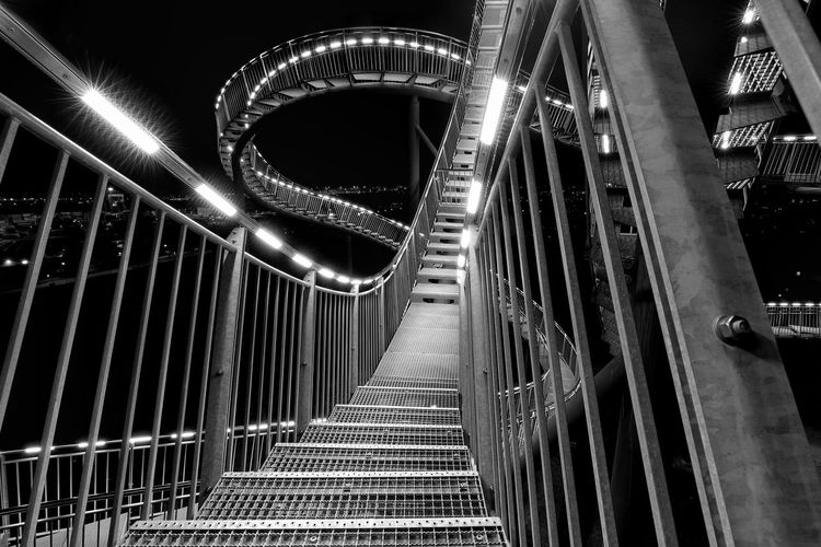 """Loops'n stairs"" https://www.facebook.com/mh.photography.de/ Https://www.facebook.com/mh.photography.de/ Michael Hruschka Duisburg Monochrome Schwarzweiß Black And White Blackandwhite Stairs Loop Looping Tiger And Turtle – Magic Mountain Tiger And Turtle Bridge - Man Made Structure Connection Railing Illuminated Night Architecture Transportation Built Structure The Way Forward No People Footbridge"
