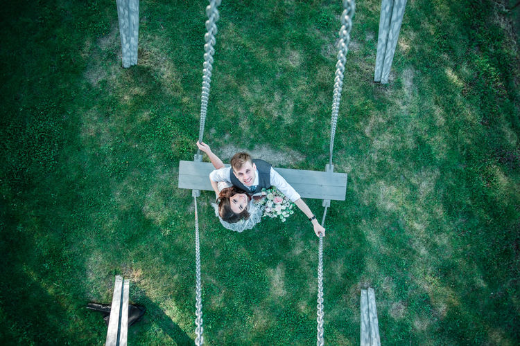 Portrait of bride and groom on swing at park