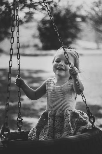 Portrait of smiling girl sitting on swing at playground