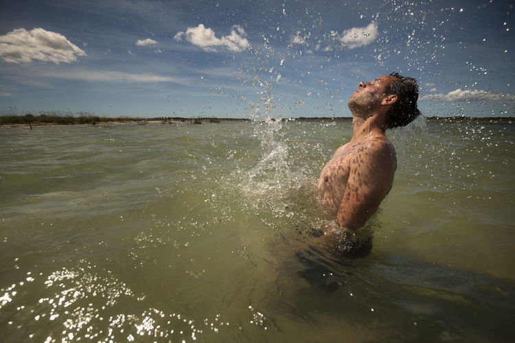 Shirtless Man Swimming In Sea Against Sky On Sunny Day