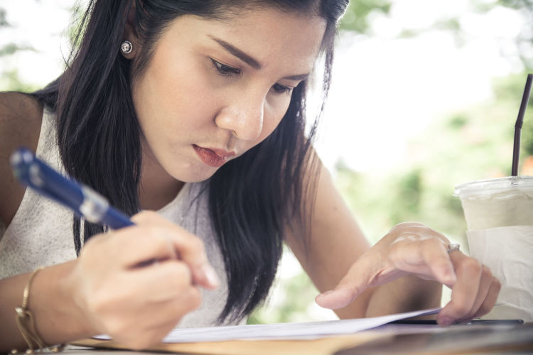 Close-up of young woman writing on paper at table