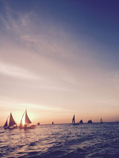 Silhouette sailboats sailing in sea against sky during sunset