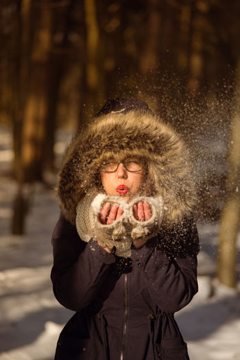Portrait Of Young Woman Blowing Snow On Field