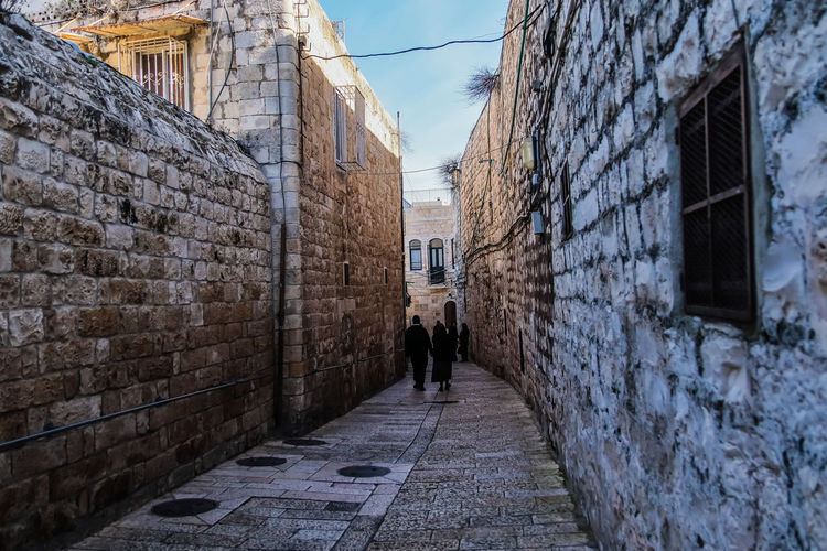 City Prison Men Walking Architecture Building Exterior Sky Built Structure Cobblestone Cobbled Alley Walkway Pavement Ivy Lane Castle Old Town Pathway Paving Stone Stone Wall Pedestrian Walkway Narrow Townhouse Fortified Wall Passage Fortress Fort Destinations Long Arched