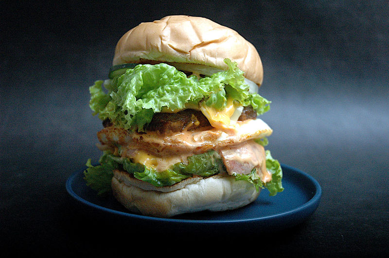 Close-up of burger in plate against black background