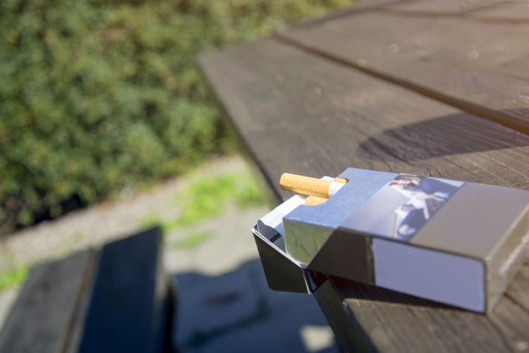 Open pack of cigarettes on the wooden table in the park Caffeine Cigarettes Tobacco Bench Box Nature No People Packaging Park Seat Table Unhealthy Wood - Material