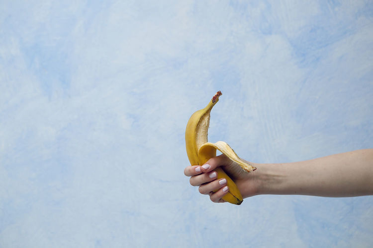 View Of Woman's Hand Holding Holding Banana
