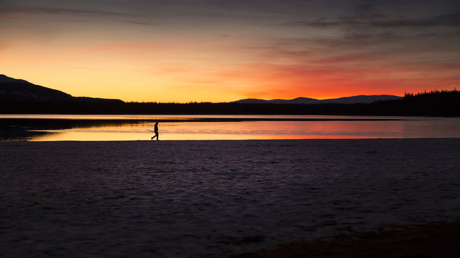 End of Fishing Day Dusk Sky Fishing Lake One Person Orange Color Silhouette Sunset Tranquil Scene Waterfront