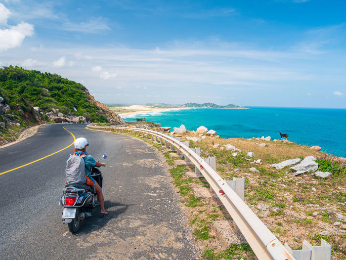 Rear view of people riding motorcycle on road by sea against sky