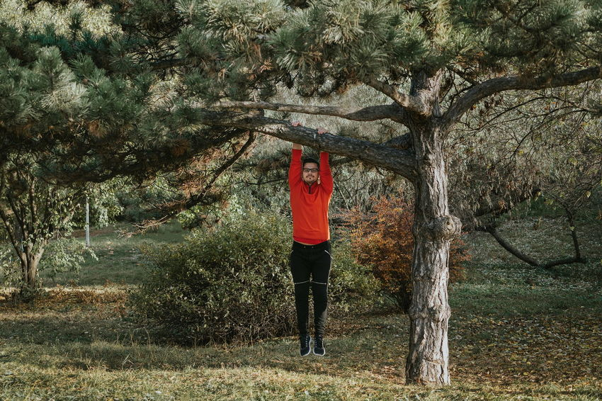 Getting in shape. Hanging Looking At Camera Exercising Men One Person One Man Only Tree Full Length Sport Standing Grass