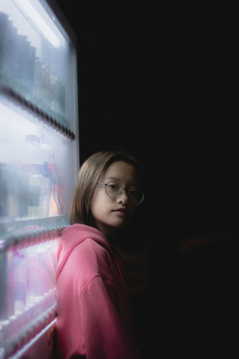 Portrait of girl standing by vending machine