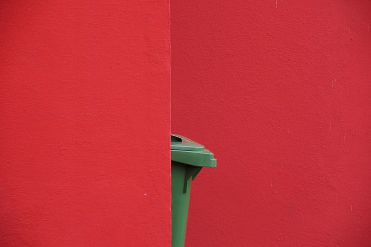 Close-up of green carbage bin against red wall