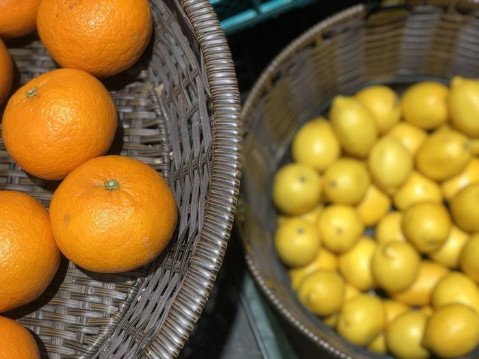 High angel view of freshness orange and blurred a pile of lemons in basket.