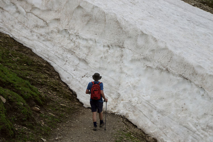 Rear view of man hiking by glacier