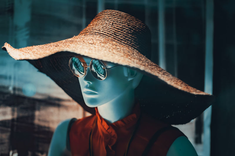 Close-up of mannequin wearing hat against window