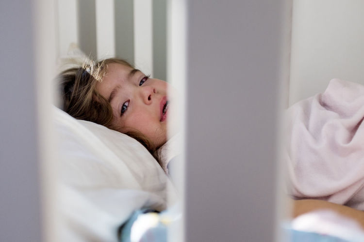 Portrait of boy resting on bed at home