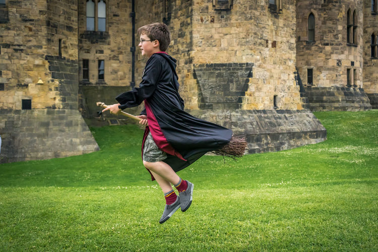 Architecture Broomstick Built Structure Carefree Casual Clothing Day Flying Full Length Grass Green Color Harrypotter Leisure Activity Lifestyles Magic Outdoors Person Tourism Wizard Young Adult Young Men