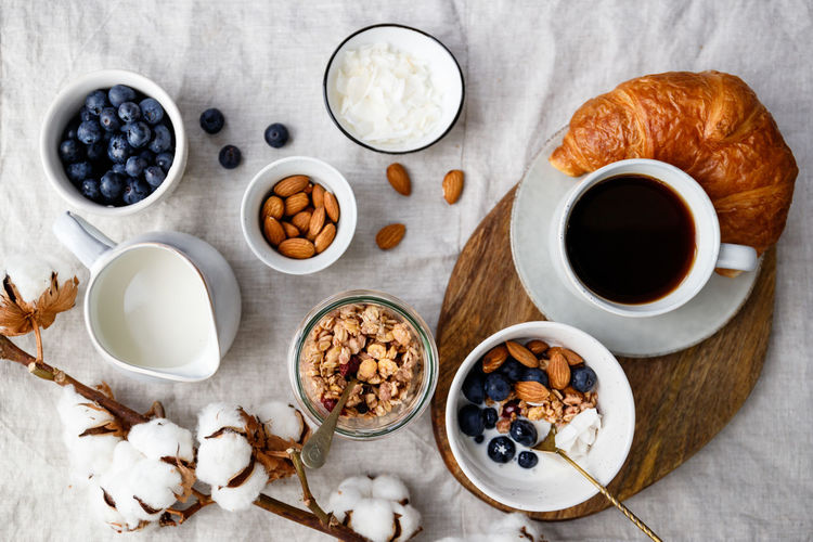 Top view of breakfast table with coffee, croissant, granola, nuts, berries and milk. Flat lay, healthy eating concept. Granola Food Breakfast Bowl Blueberry Berry Porridge Table Concept Top Flat Lay Ceramics Cereal Lifestyle Meal Holding Cotton Girl Vegan Oat Almond Chia Nuts Croissant Milk Directly  Above Two Juice Dessert Espresso Vegetarian Natural Organic Snack Sweet Muesli Yogurt View Background Seed Photography