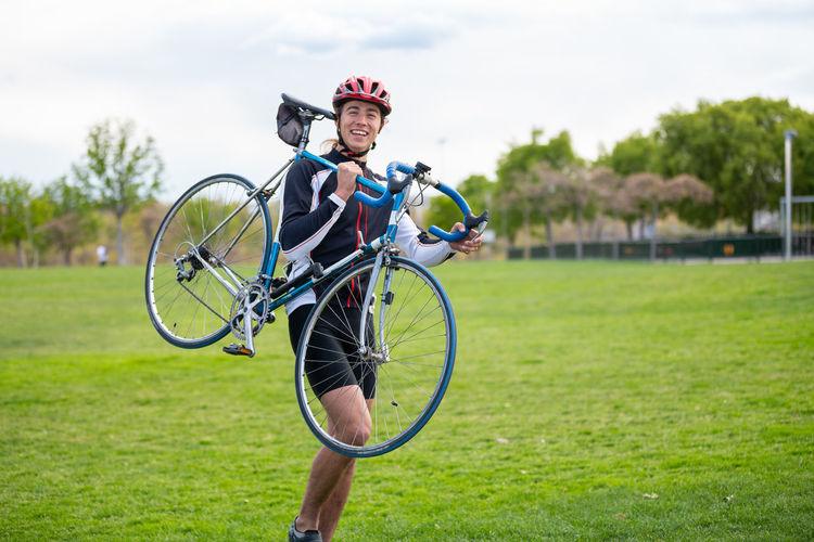 Portrait of man riding bicycle on grassland