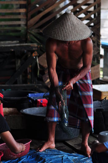 Fisherman in traditional market. midsection of man working