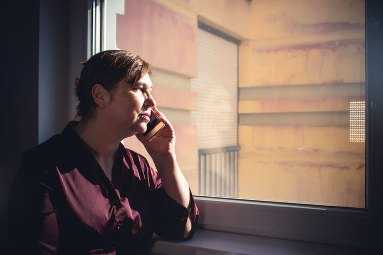 Woman talking on mobile phone while looking through window