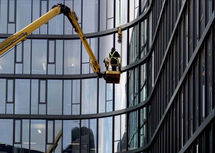 Low angle view of man working on building