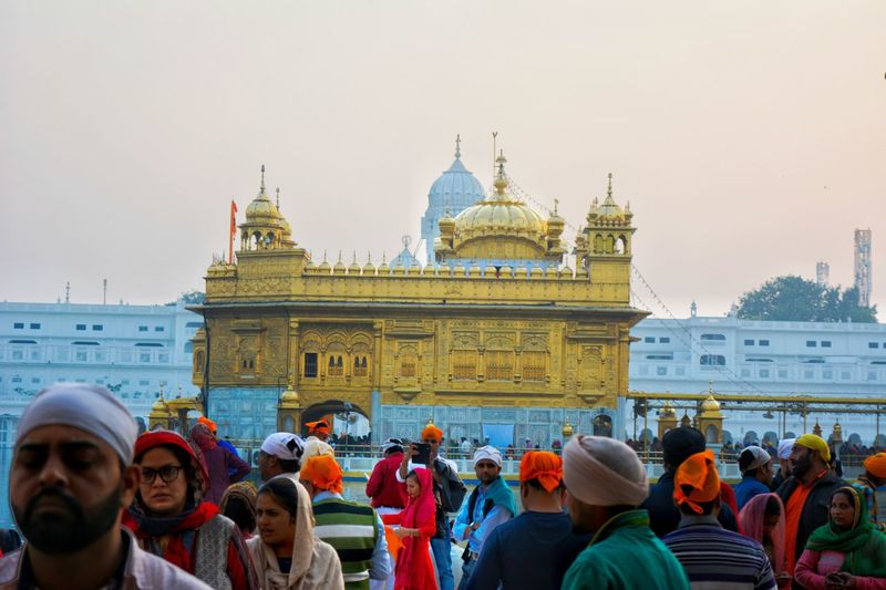 Over 100,000 people visit the holy shrine daily for worship, and also partake jointly in the free community kitchen and meal. Harmandir Sahib is house of the world's largest soup kitchen. According to Croatian Times, it can serve free food for up to 100,000 - 300,000 people every day. At the Langar (Kitchen), food is served to all visitors regardless of faith, religion, or background. To take care of such huge number of people everyday lot of man power is required and The most Beautiful thing is most of the people who work in golden temple, work out of faith with no remunerations. Golden Temple Harmandir Sahib Amritsar Golden Gold Riligion Sikhism Gurudwara Gurdwara Sprituality Spritual God Exceptional Photographs Hinduism Place Of Worship Architecture Large Group Of People Built Structure Travel Destinations Building Exterior People Dome Buliding Crowd Enjoying Life Lost In The Landscape