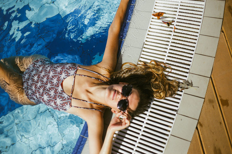High angle portrait of woman relaxing in swimming pool