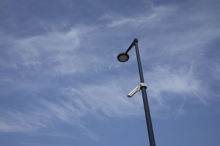 Low Angle View Of Security Camera On Street Light Against Sky