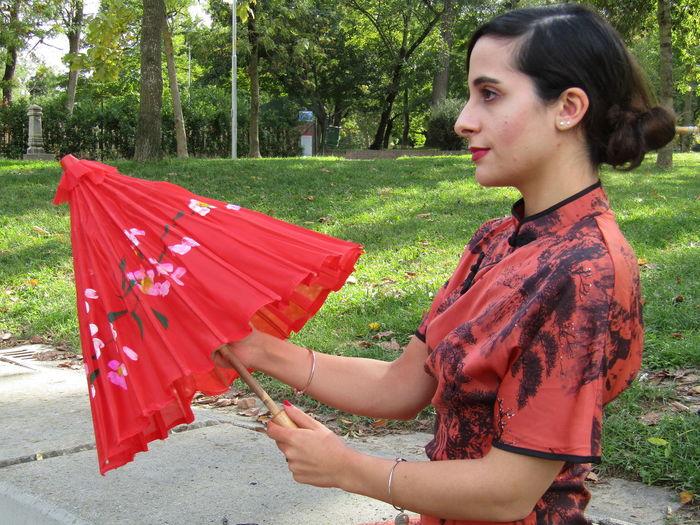 Woman closing umbrella while sitting at park