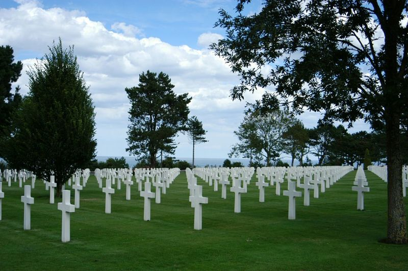 Rows of crosses on grassy field in normandy american cemetery and memorial