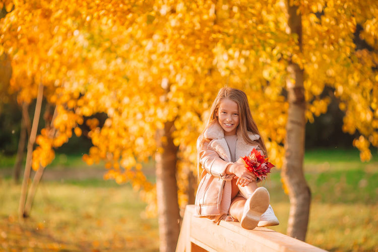 Portrait of smiling woman with autumn leaves