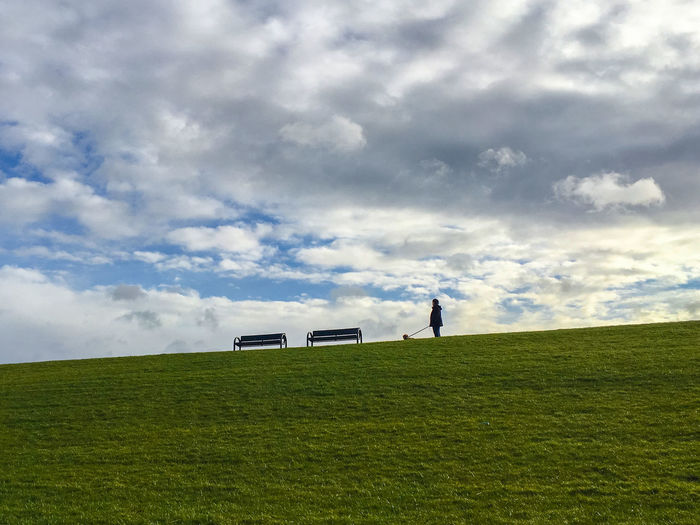 Low Angle View Of Man With Dog By Benches On Grassy Hill Against Cloudy Sky