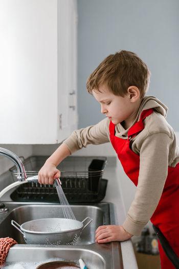 Side view of boy cleaning colander in kitchen sink