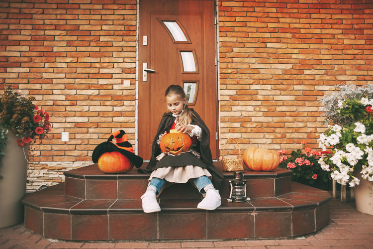Little girl dressed as a fairy with a lantern jack sits on the steps near her house during