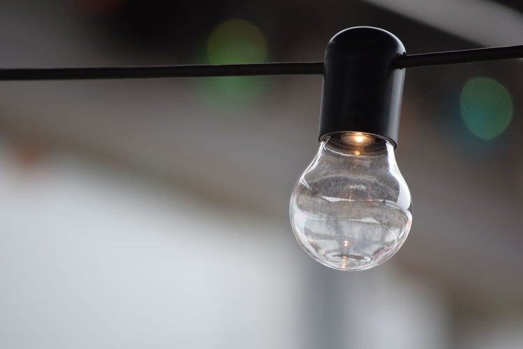 Close-up of light bulb hanging on cable