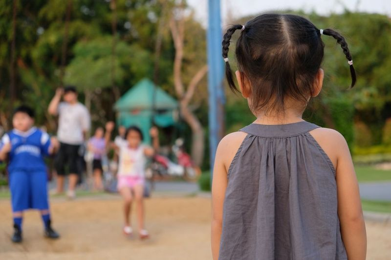 Rear view of girl standing at park