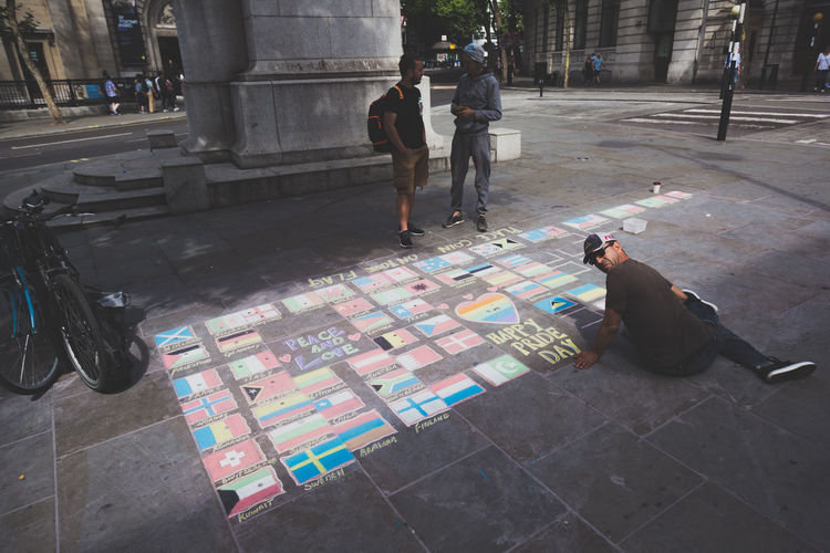 Chalk painting of the flags of the world. Artist Chalk Art Graffiti LGBT Parade London Man Press For Progress Protest Chalk Countries Day Flag Flags Graffiti Art Journalism Lgbt Lgbt Pride Lgbtq Outdoors Pavement Prideparade Protesters Rainbow Real People World Stories From The City