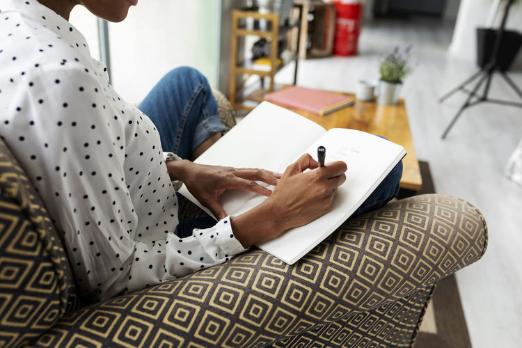 Midsection of woman reading book while sitting at home