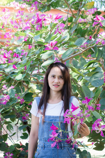 Portrait of woman with pink flower standing against plants