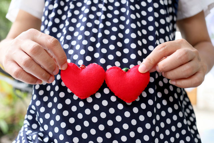 Pregnant women wear navy blue maternity clothes and a red heart symbol placed on belly. Pregnant Woman Casual Clothing Close-up Day Emotion Focus On Foreground Front View Heart Shape Holding Love Midsection One Person Outdoors Pattern Polka Dot Positive Emotion Pregnant Pregnant Belly  Pregnant Life Pregnant Phtography Real People Red Spotted Valentine's Day - Holiday Women