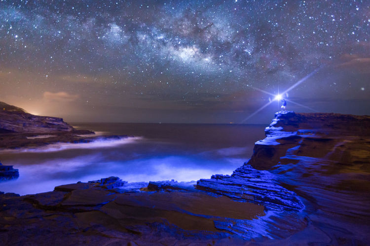 Distant view of man holding illuminated flashlight on rock at shore against star field