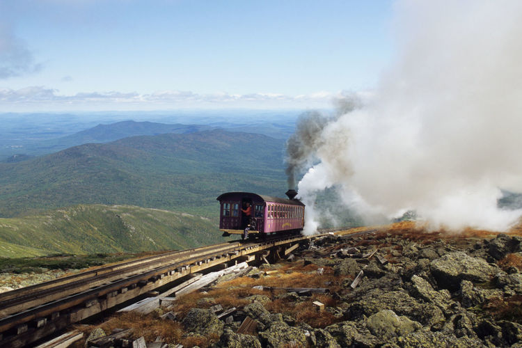 Steam locomotive pushing up Coach to the summit of of Mount Washington at good weather conditions Bretton Woods Resort Mount Washington Cog Railway Narrow Gauge Railway New Hampshire, USA United States Beauty In Nature Day Environment Land Vehicle Mode Of Transportation Motion Mountain Nature No People on the move Outdoors Pollution Public Transportation Rail Transportation Railroad Track Sky Smoke - Physical Structure Steam Train Track Train Train - Vehicle Transportation