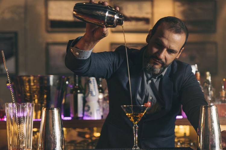 Male bartender preparing cocktail at bar counter