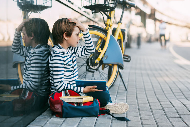 Woman using smart phone while sitting on sidewalk