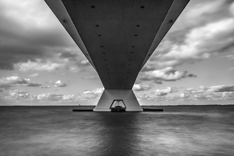 Undernear the bridge, you get the best feeling of its beauty. Architecture Cloudscape Construction Copy Space Filter Netherlands Oosterschelde Travel Architecture Black And White Bridge Bridge - Man Made Structure Built Structure Cloud - Sky Day Digital Composite Full Frame Horizon Horizon Over Water Journey Long Exposure Monument Nature No People on the move Outdoors Scenics - Nature Sea Sky Steel Tranquil Scene Transportation Water Waterfront Zeeland  Zeelandbrug The Architect - 2018 EyeEm Awards
