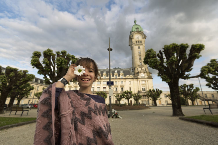 11-year-old Spanish girl in front of the limoges station in France. Limoges Tourist Travel Architecture Building Exterior Casual Clothing Cloud - Sky Day Emotion Front View Girl Hairstyle Happiness Nature One Person Outdoors Plant Portrait Sky Smiling Standing Travel Destinations Tree Waist Up Young Women